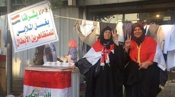 أم سلوان وأم علي في مغسلة الاحتجاجات (رويترز)