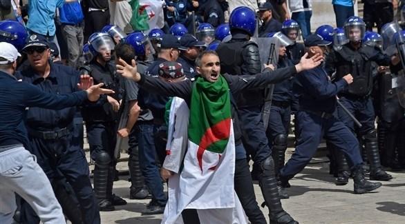 متظاهر يرتدي العلم الجزائري أمام عدد من عناصر الشرطة (أرشيف)
