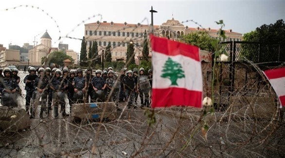 العلم اللبناني معلقاً على السياج الشائك أمام القوى الأمنية في بيروت (أرشيف)