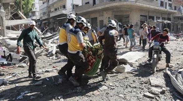 مسعفون من الخوذ البيضاء ينقلون أحد المصابين في غارة للنظام على إدلب (أرشيف)