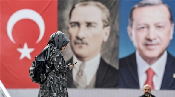 امرأة تقف قبالة صورة ضخمة لأردوغان (أرشيف)