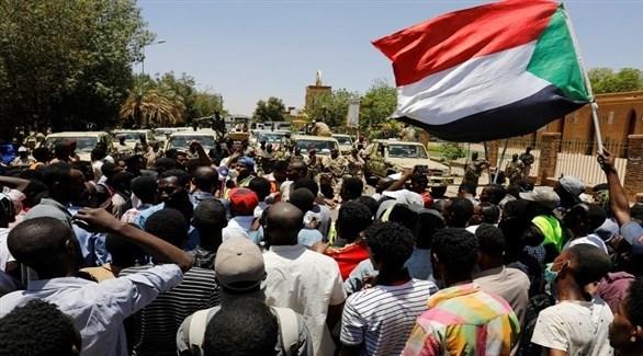 متظاهرون سودانيون يهتفون أمام قوات الأمن (رويترز)