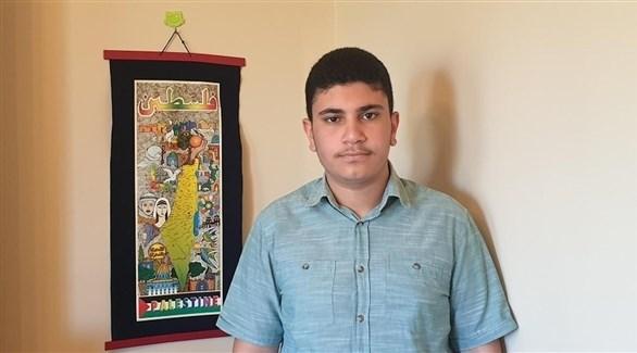 الطالب اسماعيل عجاوي وخلفه خريطة فلسطين (إندبندنت عربية)