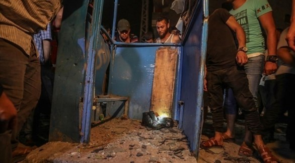 فلسطينيون يُعاينون آثار أحد التفجيرين في غزة أمس الثلاثاء (تويتر)