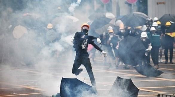 متظاهر يرمي أسطوانة الغاز المسيل للدموع على الشرطة (أ ف ب)