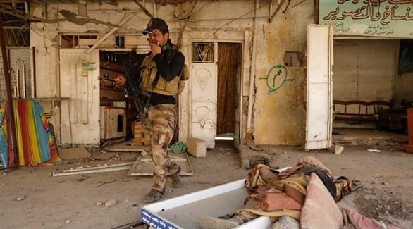 عسكري عراقي أمام جثة في أحد شوارع الموصل (أرشيف)