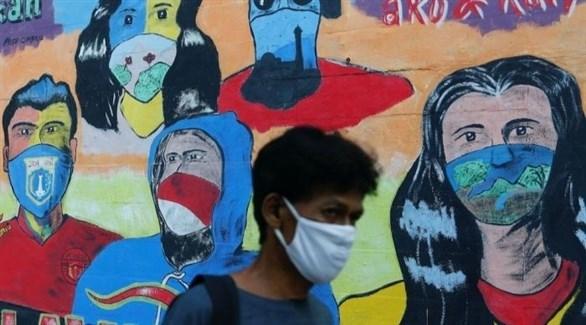 شخص يمر بجانب جدارية تعكس جهود مكافحة كورونا في جاكرتا (أرشيف)