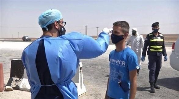 ممارس صحي يفحص درجة حرارة مواطن في الأردن (أرشيف)