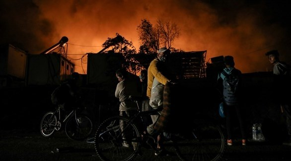 لاجئون يتابعون الحريق في مخيم موريا اليوناني (أرشيف)