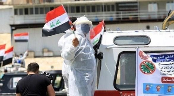 عامل في القطاع الصحي العراقي يرفع علم بلاده (أرشيف)