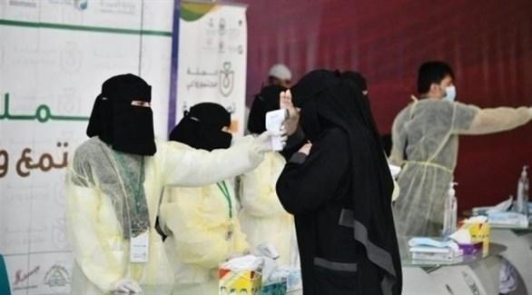 عاملة في القطاع الصحي السعودي تفحص سيدة في مركز صحي متنقل (أرشيف)