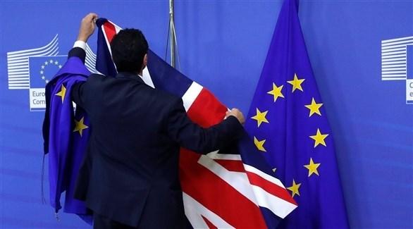 موظف في المفوضية الأوروبية يمسك علم بريطاني وراية الاتحاد الأوروبي (أرشيف)