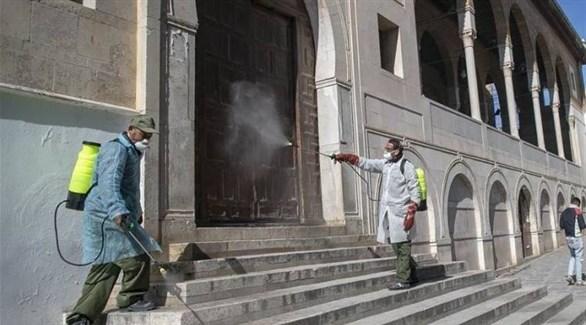 عاملان يُعقمان إحدى بوابات جامع الزيتونة في المدينة العتيفة (أرشيف)