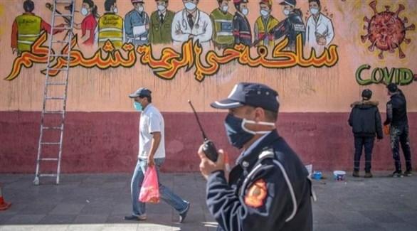 مغاربة أمام جدارية للتوعية بكورونا في الدار البيضاء (أرشيف)
