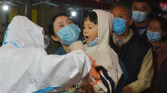 طبيب صيني يأخذ مسحة من طفل لفحص كورونا (إ ب أ)