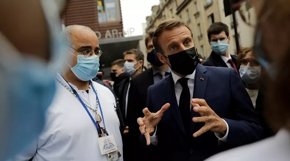 الرئيس الفرنسي إيمانويل ماكرون يتحدث إلى عاملين في القطاع الصحي (رويترز)