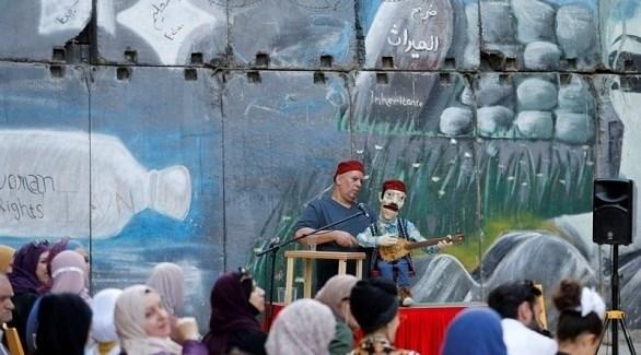 الفلسطيني عبد السلام عبده ودميته عازفة العود (تويتر)