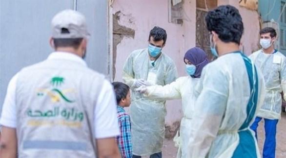 عاملون في القطاع الصحي السعودي مع طفل (أرشيف)