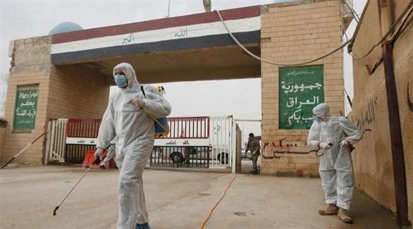 عاملان عراقيان يُعقمان معبراً حدودياً برياً (أرشيف)