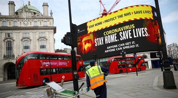 عامل نظافة في لندن أمام جدارية تدعو للبقاء في البيوت (أرشيف)