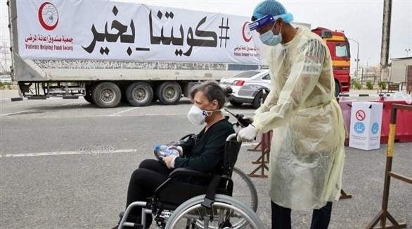 عامل في القطاع الصحي الكويتي يدفع سيدة على كرسي متحرك (أرشيف)