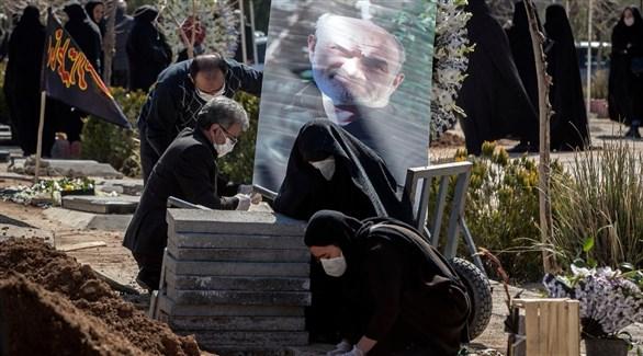إيرانيون في مقبرة حول قبر أحد ضحايا كورونا (أرشيف)