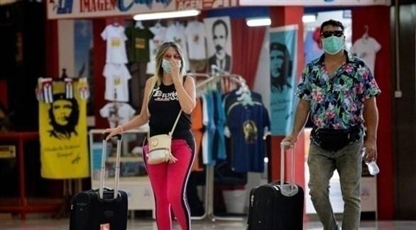 رجل وامرأة يرتديان الكمامة الصحية خوفاً من كورونا في كوبا (أرشيف)