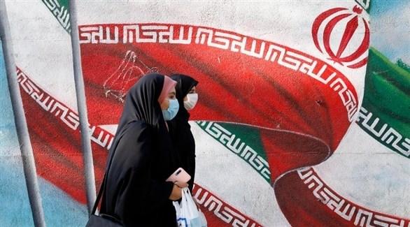إيرانيتان أمام صورة لعلم بلادهما (إ ب أ)