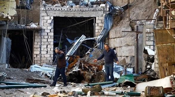 مدنيان وسط أنقاض مبنى هدمه القصف في ناغورنو قره باخ (رويترز)