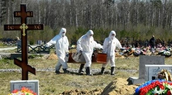عاملون في مقبرة روسية ينقلون تابوت أحد ضحايا كورونا (أرشيف)