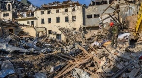 عسكري أذري يبحث عن ناجين بين أنقاض مبنى تعرض لقصف في كنجة (أ ف ب)