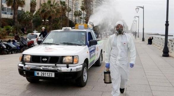 عامل في قطاع الصحة اللبناني إلى جانب سيارة تعقيم في كورنيش بيروت (أرشيف)