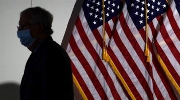 أمريكي يمر بجانب علم بلاده (أ ف ب)