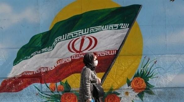 سيدة إيرانية تمر بجانب جدار مرسوم عليه علم بلادها (أ ف ب)