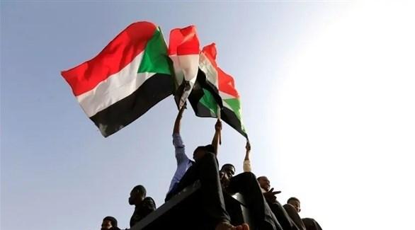مجموعة من الشبان يرفعون العلم السوداني (أرشيف)