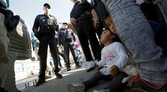 عناصر أمنية تقف قبالة مجموعة من الأطفال على الحدود مع الولايات المتحدة (أرشيف)