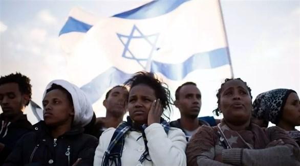 مجموعة من المهاجرين وبدا العلم الإسرائيلي في الخلف (تعبيرية)