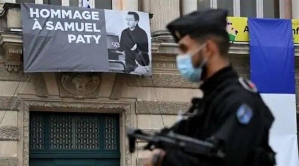 عنصر من الشرطة الفرنسية أمام لافتة لتكريم مدرس التاريخ صامويل باتي (أرشيف)