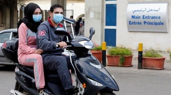 لبنانيان على دراجة نارية أمام مستشفى رفيق الحريري في بيروت (أرشيف)
