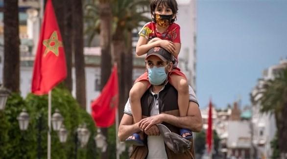 مغربي يحمل طفلاً على كتفيه (أرشيف)