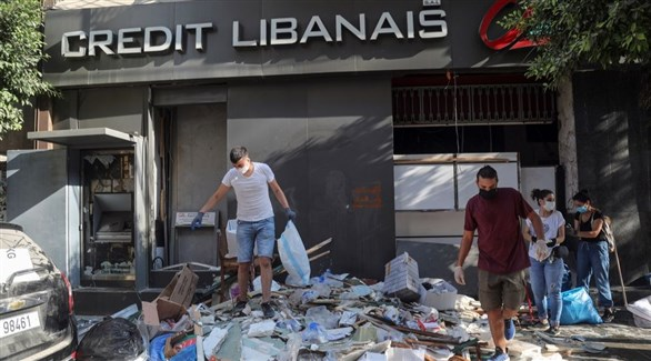 لبنانيون وسط نفايات وأنقاض أحد شوارع ببيروت (أرشيف)