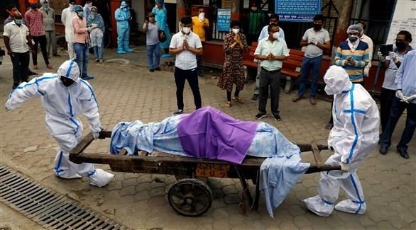 عاملان بقطاع الصحة الهندي ينقلان جثة أحد ضحايا كورونا (ارشيف)