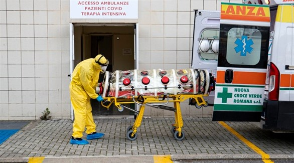 مسعف ينزل مصاباً بكورونا من سيارة إسعاف أمام طوارئ مستشفى في روما (أنسا)
