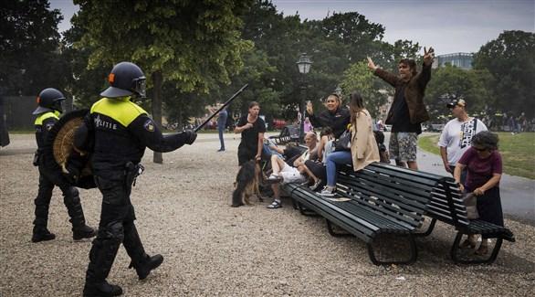 شرطيان هولنديان يفرقان شباناً في حديقة عامة غير ملتزمين بالإجراءات الصحية (أرشيف)