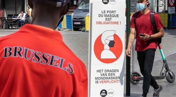 بلجيكيان أمام لوحة تذكير بإلزامية وضع الكمامات في بروكسل (أرشيف)