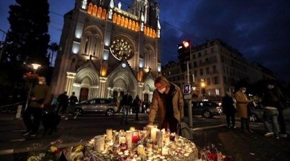 فرنسيون يشعلون شموعاً أمام كنيسة نوتردام بعد الهجوم الإرهابي (أ ف ب)
