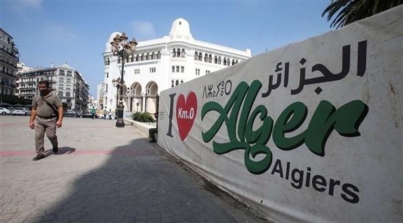 جزائري أمام جدارية أحب الجزائر بالعربية والفرنسية والأمازيغية (أرشيف)