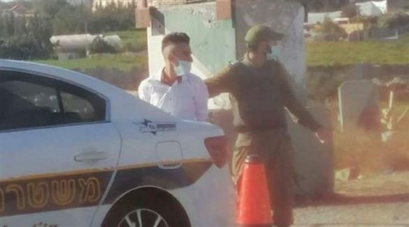 جندي إسرائيلي يعتقل فلسطينياً على تقاطع طرق غوش عتصيون (تويتر)