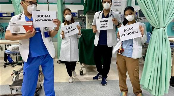 عاملون في القطاع الصحي الفلبيني يُذكرون بقواعد الوقاية من كورونا (أرشيف)