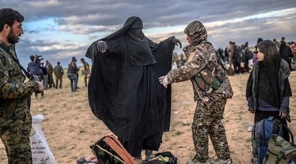 مجندة كردية في العراق تفتش سيدة من عائلات مقاتلي داعش (أرشيف)
